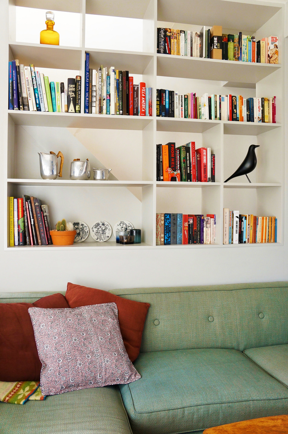 Scandinavian Inspired Living Room Bookshelf Featuring Vitra Eames House Bird